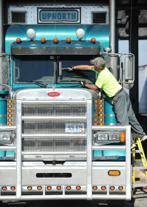 Chuck Trafton cleans the windshield on a truck at the pumps at Dysart's Truck Stop in Hermon on Tuesday. Most truckers say the biggest threat to truck driving safely is cars cutting them off, not understanding that they can't swerve or brake hard to avoid an accident.