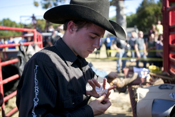 Seventeen-year-old David Harding of Shirley, Maine, tapes his left hand prior to competing in the bull riding competition at the Cumberland County Fair, Saturday, Sept 28, 2013.
