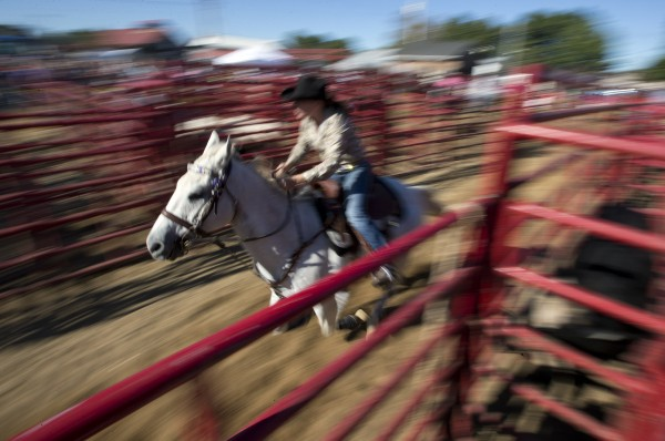 A competitor in the girls barrel race charges out of the gate at the Cumberland County Fair, Saturday, Sept 28, 2013.