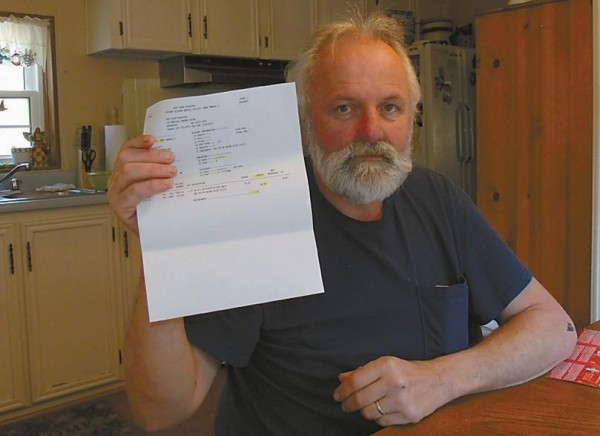 Don Adams holds a patient record belonging to a Newcastle woman before tearing it up to protect her identity on Thursday at his Woolwich home. The record was sent to him by Mid Coast Hospital.