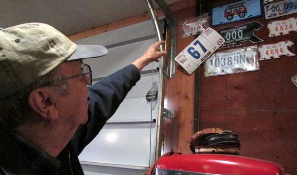 Jack Greenleaf of Oxford points out his collection of license plates from Canada.