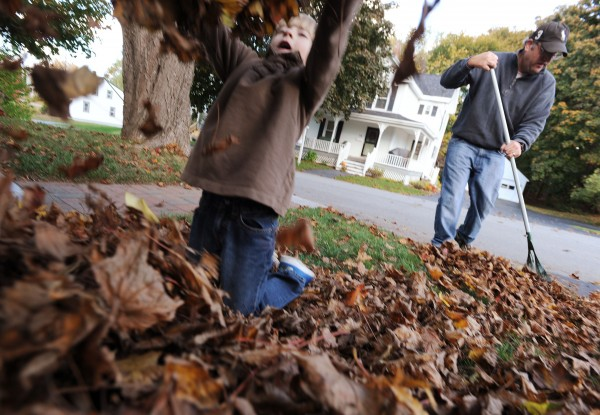 Max Gatchell plays in the leaves that he raked together at his home in Brewer on Sunday as his father Jason continues where Max left off.