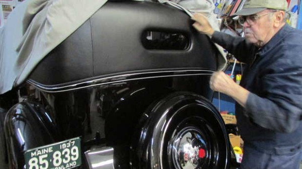 Jack Greenleaf pulls the cover off a lovingly restored 1937 Packard in his workshop on King Street in Oxford.