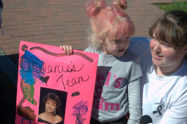 Addyson Melrose Randall, 3, of West Bath holds a sign in memory of her grandmother, Melanie Strout Randall of Bradford, who died of cancer in 1999. Addyson raised $600 for the Susan G. Komen Race for the Cure held in Bangor on Sunday, Sept. 15.