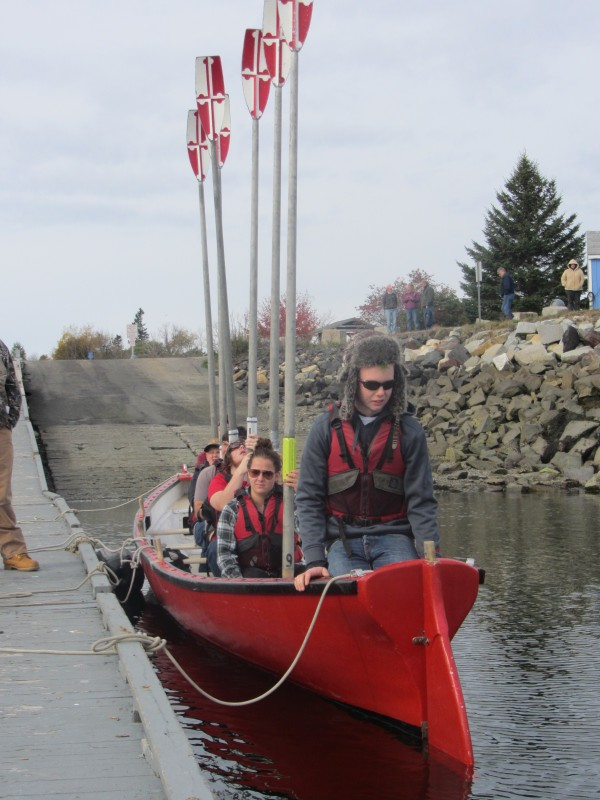 The Station Maine team holds up their oars before rowing out to begin a race Saturday in Rockland Harbor.