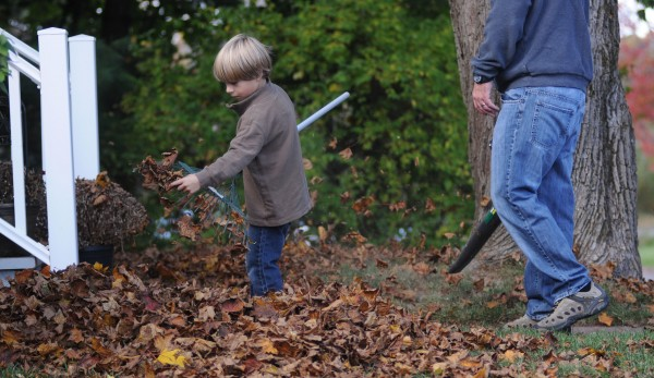 Max Gatchell rakes leaves at his home in Brewer on Sunday as his father Jason cleans up with a leaf blower.