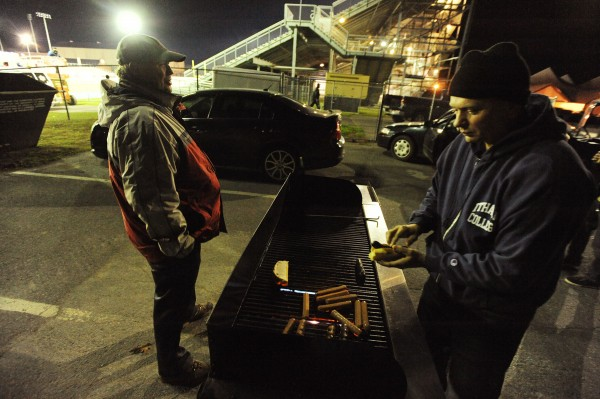 Orono High School principal Jim Chasse (right) cooks hot dogs on a grill next to Morse Field on the UMaine campus as Pike Bartlett (left) prepares to watch his first ever high school football game as Orono and John Bapst football teams play the last regular season game a Thursday night.