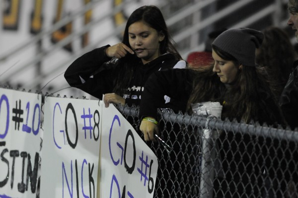John Bapst students Shaylyn Cyr (left) and Kennedy Gerow (right) post signs supporting the school's football players along the fence on the visitors side of Morse Field on the UMaine campus in Orono on Thursday night.