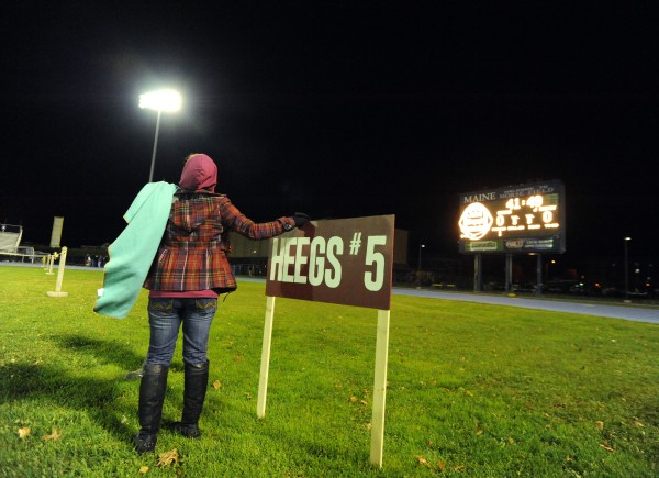 Janis Veillette prepares to post a sign with her son's nickname and jersey number on it before the Orono, John Bapst football game at Morse Field on the UMaine campus in Orono on Thursday night.