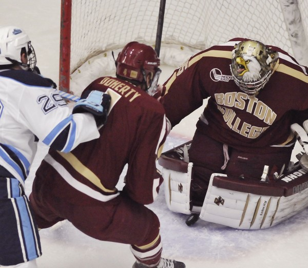 Maine winger Connor Leen (29) tries to get around Boston College defenseman Teddy Doherty (4) as goalie Parker Milner (1) makes a save during a game last November. Leen and Ryan Lomberg are Maine's top returning goal scorers with seven each last season.