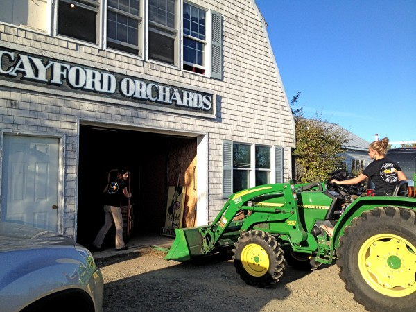 Cortlynn Davis brings the tractor into the packing house as mom Heather Davis looks on.