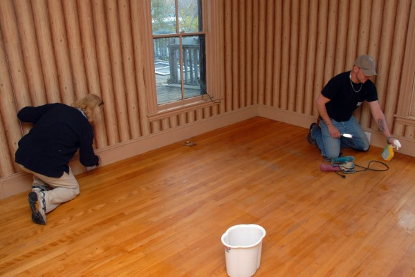 Dennis Smith, left, and Wade Davis scrape stains from the floor at 19 Central St. during renovations on Friday, Oct. 25, 2013.