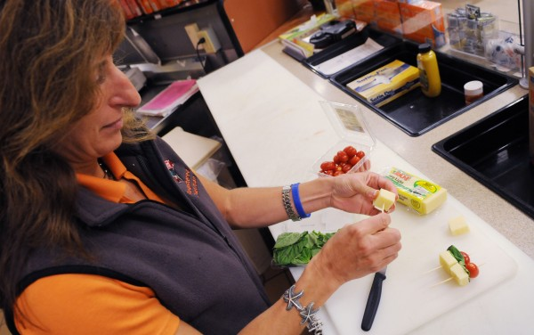 Registered dietitian Mary Lavanway at Hannaford assembles a cheese, basil and cherry tomato snack that she recommends for healthy weekend football tailgating.