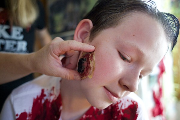 Amy Violette puts a fake boil on her son, Nathaniel Cusack's, 12, face at their home Monday afternoon in Bucksport. Violette does makeup for various Halloween events around town including Fright at the Fort.