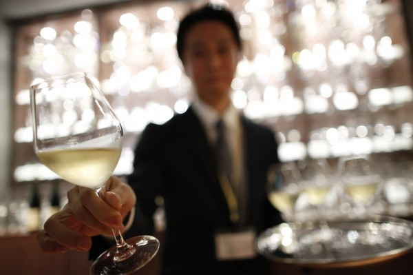 Tomonori Kakita, a sommelier-cum-concierge, demonstrates how to serve wine during a press preview at the Wine Apartment in Tokyo September 30, 2013.