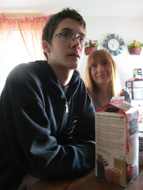Kai McGee, 15, sits in his Westbrook home with his mother, Gloria Caricchio on Oct. 3, 2013. McGee, who has a severe milk allergy, must avoid many foods and substitute with soy milk and soy ice cream, or risk a dangerous immune reaction.