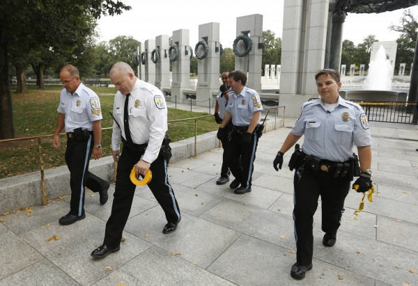 U.S. Park Police walk away after closing the World War II Memorial in Washington October 1, 2013.