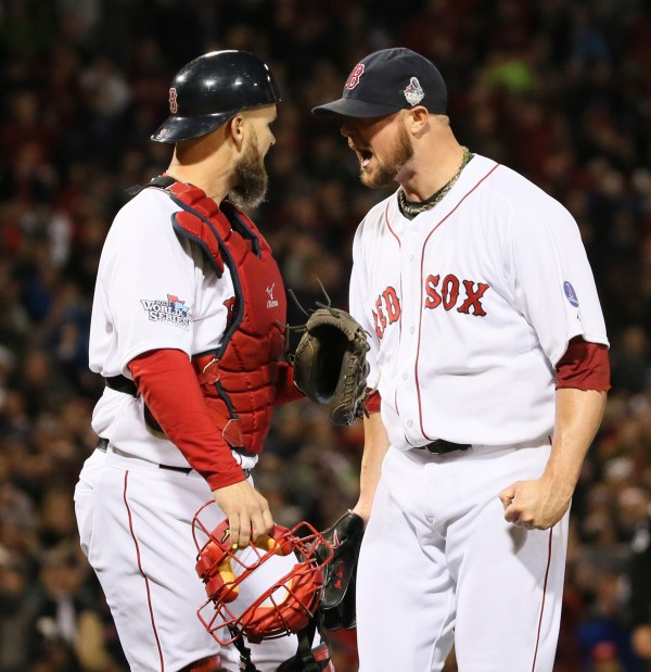 Boston Red Sox catcher David Ross, left, and starting pitcher Jon Lester celebrate after Lester started a double play on a ground ball by the St. Louis Cardinals' David Freese to end the top of the fourth inning in Game 1 of the World Series at Fenway Park in Boston, Massachusetts, on Wednesday, October 23, 2013. Boston won, 8-1.