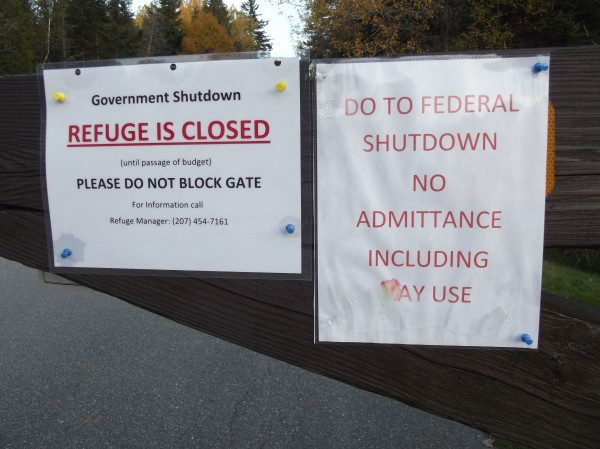 Close-up views of gate to Cobscook Bay State Park shows notices informing visitors that the park has been closed due to the shutdown of the federal government.