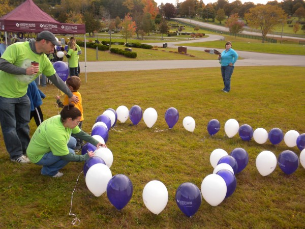 Glenburn resident Anette Poulin writes the name of her first born son, Jonas, on one of the balloons tied to the ground in the shape of a heart at the Empty Arms Remembrance Walk on Saturday, Oct. 5, 2013. Her husband, Christopher, and second son stand behind her. &quotIt will be five years in November and it's still hard,&quot Poulin said about missing Jonas.