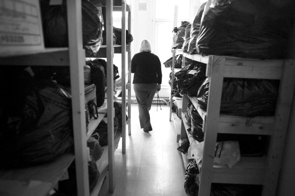 Program Manager Rowena Griffin walks through shelving that contains bags of belongings that some of Bangor's homeless have been allowed to leave at the shelter in September.