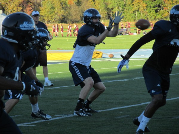 John Ebeling takes a snap at quarterback during a recent practice in Orono. The senior has been a productive wide receiver and long-snapper for the Black Bears.