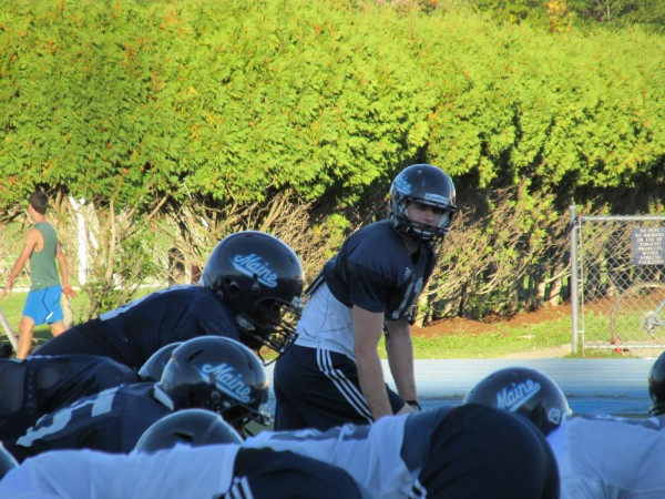 University of Maine senior football player John Ebeling (top) lines up to run a play during a recent practice in Orono.