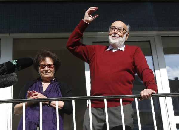 Belgian physicist Francois Englert reacts next to his wife Mira as they appear at the balcony of his house in Brussels October 8, 2013, after he and Britain's Peter Higgs Peter won the 2013 Nobel prize for physics. The two scientists won the prize for predicting the existence of the Higgs boson - the particle key to explaining why elementary matter has mass - the award-giving body said on October 8.