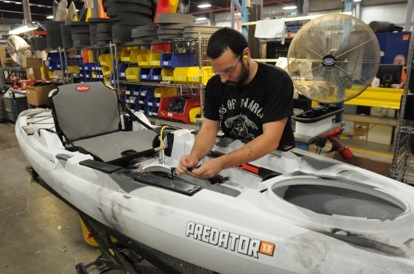 Trevor Grey bolts hardware to the company's new Predator watercraft at Johnson Outdoors in Old Town in June.