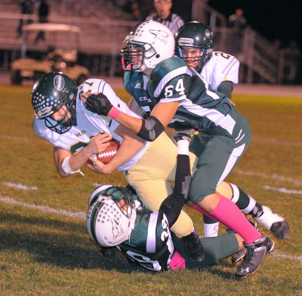 Mount Desert Island High School's Santos Henggeler (left) is tackled by Old Town High School's Braden Upshaw (bottom) and Logan Hildreth during the first half in Old Town Friday evening. MDI won 42-22 and the two teams will meet again this Friday night in Bar Harbor in a first-round playoff game.
