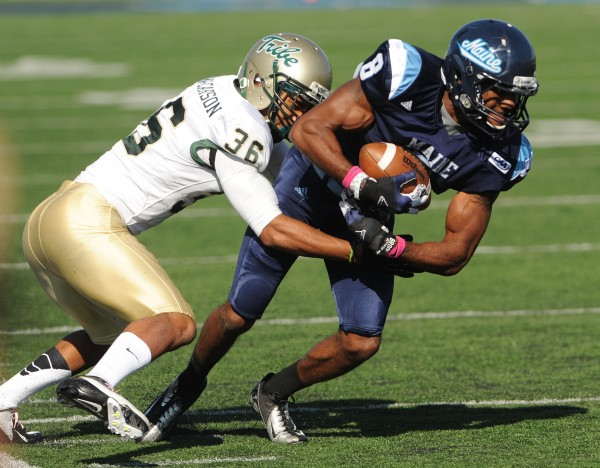 William and Mary's DeAndre Huston-Carson brings down UMaine's Michael Cote during first-half action Saturday in Orono.