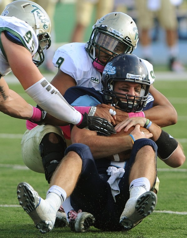 University of Maine quarterback Marcus Wasilewski is sacked by William and Mary's Quincey September and Mike Reilly during second-half action at Orono on Saturday.