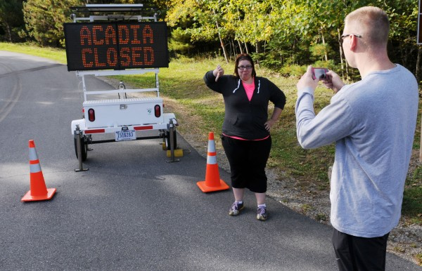 Jonathan Coultas takes a picture of his wife, Nicole, in front of a sign informing tourists that Acadia National Park is closed due to the federal government shutdown. The couple traveled from Neenah, Wis., to Mount Desert Island to celebrate their fifth wedding anniversary. They hope the park will open soon, as they plan to stay for a week.