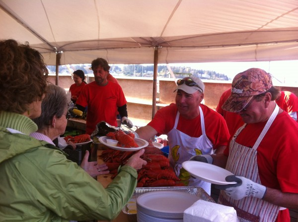 Gerry Cushman of Port Clyde, who was part of a group of Port Clyde fishermen who donated 2,000 pounds of lobsters, dishes one up Saturday at Rock the Dock in Port Clyde.