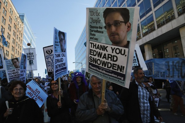 Demonstrators hold signs supporting fugitive former NSA contractor Edward Snowden as they march at the &quotStop Watching Us: A Rally Against Mass Surveillance&quot near the U.S. Capitol in Washington, October 26, 2013.
