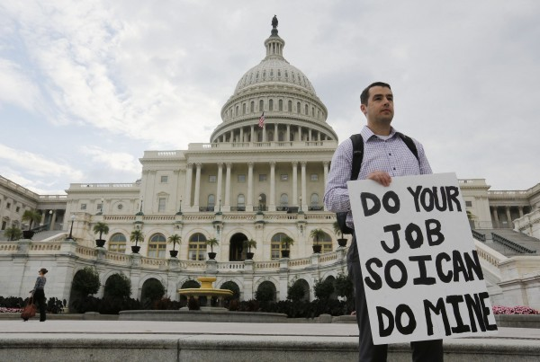 A furloughed federal employee holds a sign on the steps to the U.S. Capitol after the U.S. Government shut down last night, on Capitol Hill in Washington October 1, 2013.