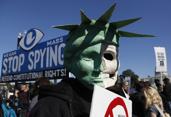 A protester wears a mask depicting a skull beneath the head of the Statue of Liberty, as he demonstrates during the &quotStop Watching Us: A Rally Against Mass Surveillance&quot near the U.S. Capitol in Washington, October 26, 2013.
