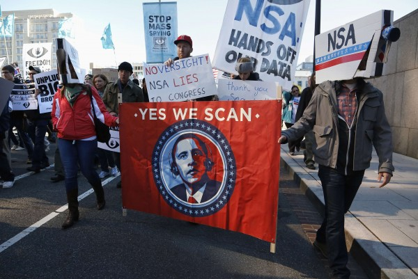 Demonstrators wearing cardboard surveillance camera hats carry a sign depicting  President Barack Obama at the &quotStop Watching Us: A Rally Against Mass Surveillance&quot march  in Washington, October 26, 2013.