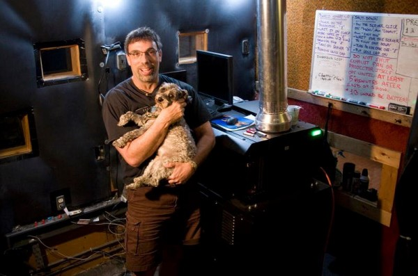 Eveningstar Cinema owner Barry Norman holds his dog, Scooter, next to the Brunswick theater's new digital projector, a purchase that upgraded the theater while putting a strain on its finances.