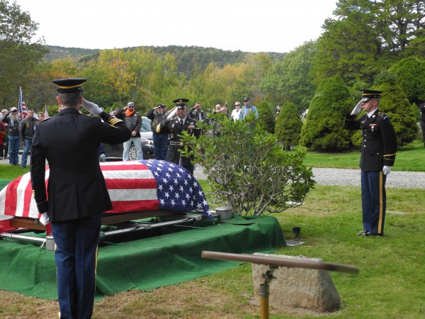 Military officials salute  the flag-covered casket of Army Cpl. Robert Tait, who was listed as missing during the Korean War. His remains recently were identified and returned to Maine for burial at Ledgelawn Cemetery with full military honors before family members, veterans and dignitaries, including Gov. Paul LePage.