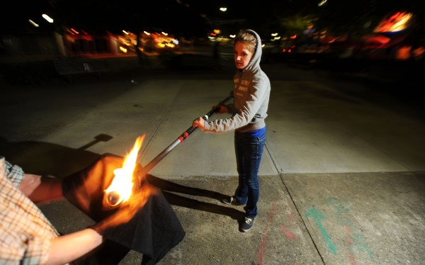 Christina Price gets help extinguishing  a fire staff from her boyfriend Mike Conley at West Market Square in Bangor on Thursday. Both Price and Conley are fire spinners with Flames of Hope a project to raise money for charity.