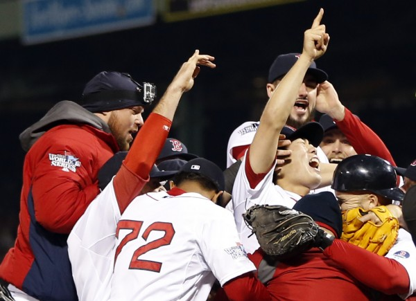 Boston Red Sox relief pitcher Koji Uehara (19) celebrates with teammates after defeating the St. Louis Cardinals in game six of the MLB baseball World Series at Fenway Park. Red Sox won 6-1.