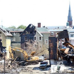 Todd Gendron from Gendron & Gendron uses his excavator to demolish the building on Blake Street in Lewiston Tuesday afternoon after Monday's devastating fire that destroyed three buildings, displacing 35 families.