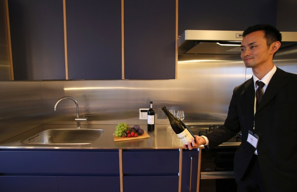 Wataru Iwamoto, a sommelier-cum-concierge, demonstrates how to serve wine inside a room during a press preview at the Wine Apartment in Tokyo September 30, 2013.