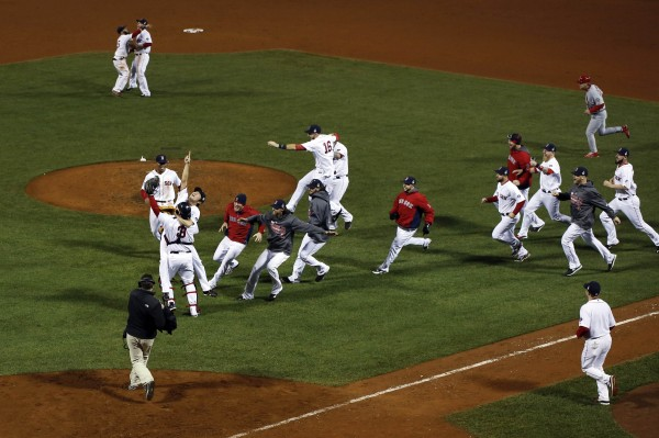 Boston Red Sox relief pitcher Koji Uehara (19) reacts with catcher David Ross (3) and teammates after defeating the St. Louis Cardinals in game six of the MLB baseball World Series at Fenway Park. Red Sox won 6-1.