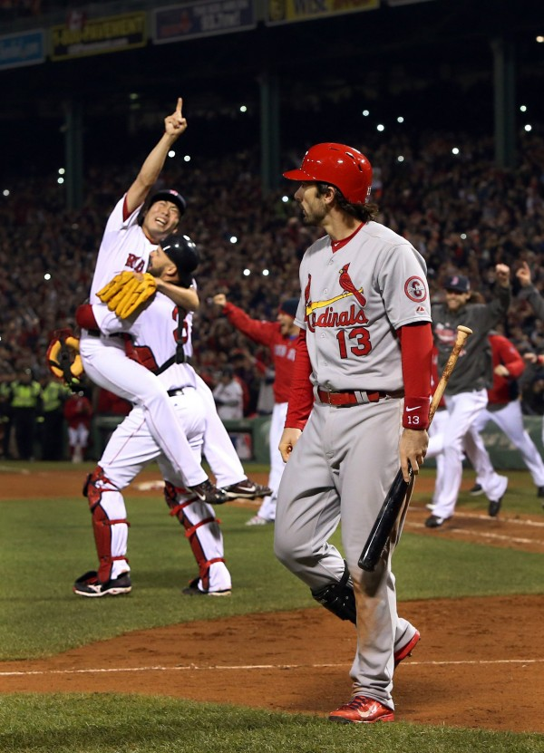 The St. Louis Cardinals' Matt Carpenter (right) walks off after striking out to end the game as the the Boston Red Sox begin to celebrate at Fenway Park in Boston, Massachusetts, on Wednesday, Oct. 30, 2013. The Red Sox won, 6-1, to clinch the championship.