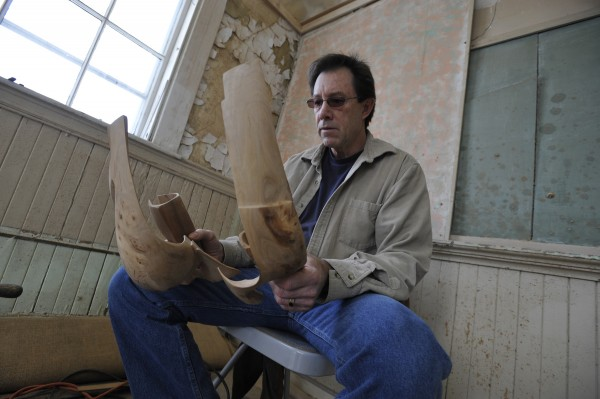 Artist Randy Colbath inspects two pieces of apple wood that he has intricately carved over one month into a geometric sculpture at his Bangor studio in February 2011.