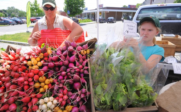 Hanne Tierney (left) and her daughter Edith set up their stand at the Waterville Farmers Market in mid-June.