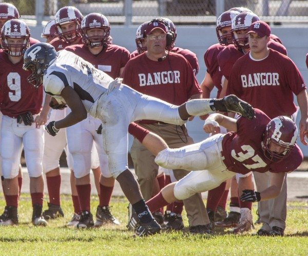 Portland High School running-back Jayvon Pitts-Young (4) shakes a tackle attempt by Bangor linebacker Evan McAuliffe (37) on the Bangor High School sideline in front of Bangor coach Mark Hackett in the second half of a football game Saturday, Sept. 28, 2013 in Bangor, Maine.