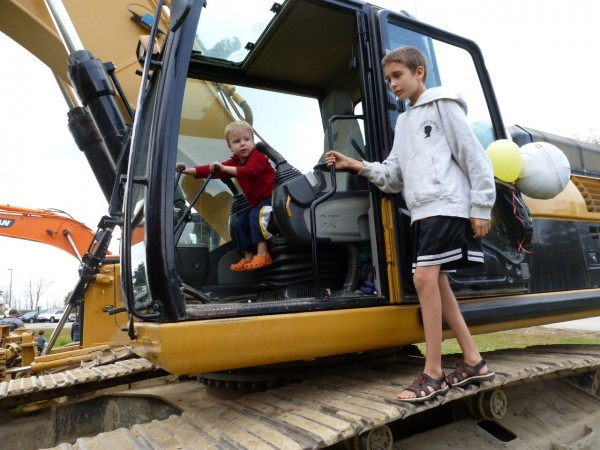 Silas Leavitt (left), 2, of Bangor works the controls of a front loader while his older brother Colby Leavitt, 9, of Bangor waits his turn Saturday during a ground breaking ceremony for St. Joseph Healthcare's medical office building at 900 Broadway. The event included an opportunity for people of all ages to explore construction vehicles.